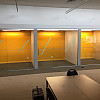 71977 coloured painted glass glued to walls to create a writing board inside office rooms that are enclosed with glass walls and sliding glass doors