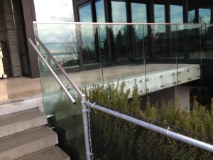 Custom glass railing system for home. This glass railing was frameless with thick safety glass. Custom bolts were used for securing glass railing to place
